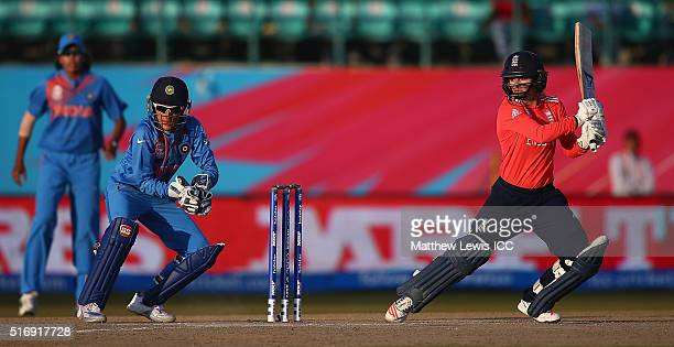 Danielle Wyatt of England hits the ball towards the boundary as Sushma Verma of India looks on during the Women's ICC World Twenty20 India 2016 match...