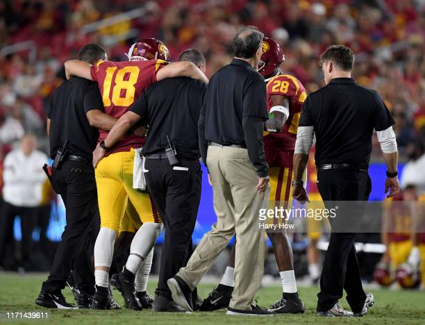 Daniels of the USC Trojans is helped off the field during the second quarter against the Fresno State Bulldogs at Los Angeles Memorial Coliseum on...