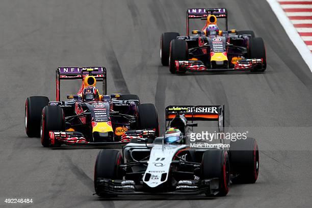 Daniil Kvyat of Russia and Infiniti Red Bull Racing and Daniel Ricciardo of Australia and Infiniti Red Bull Racing drive behind Sergio Perez of...
