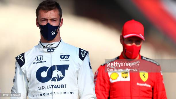 Daniil Kvyat of Russia and Scuderia AlphaTauri and Sebastian Vettel of Germany and Ferrari look on as they stand on the grid prior to the F1 Grand...