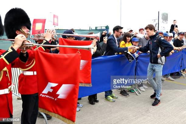 Daniil Kvyat of Russia and Scuderia Toro Rosso signs autographs for fans as Queens Guards wearing traditional bearskin hats play horns at the paddock...