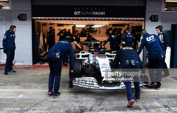 Daniil Kvyat of Russia driving the Scuderia AlphaTauri AT01 Honda is helped into the garage by Scuderia AlphaTauri team members during Day Three of...