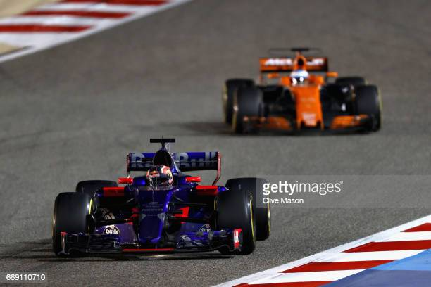 Daniil Kvyat of Russia driving the Scuderia Toro Rosso STR12 leads Fernando Alonso of Spain driving the McLaren Honda Formula 1 Team McLaren MCL32 on...