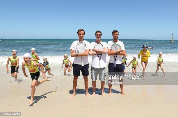 Daniil Medvedev Marat Safin and Karen Khachanov of Russia pose as Surf Life Saving nippers run from the water ahead of the 2020 ATP Cup Group Stage...
