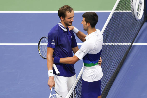 Daniil Medvedev of Russia and Novak Djokovic of Serbia talk at center court after Medvedev won their Men's Singles final match on Day Fourteen of the...