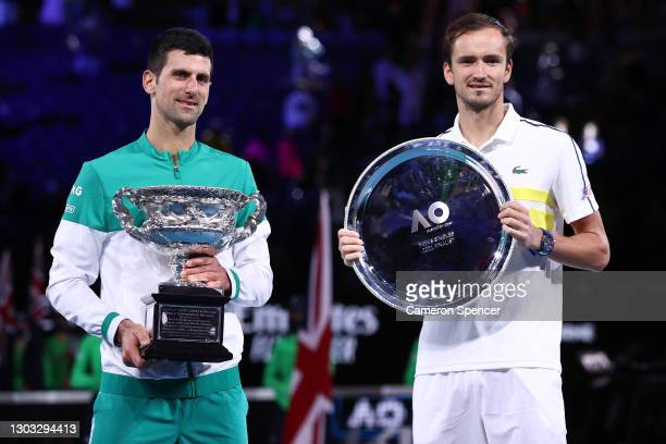 Daniil Medvedev of Russia holds the runners up plate as Novak Djokovic of Serbia holds the Norman Brookes Challenge Cup as he celebrates victory in...