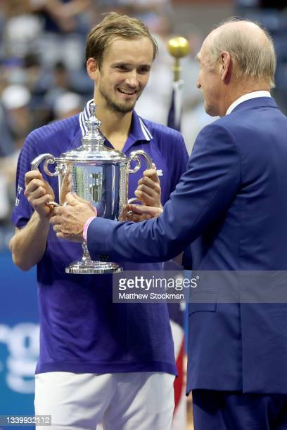 Daniil Medvedev of Russia is awarded the championship trophy by former tenner player, Stan Smith, after defeating Novak Djokovic of Serbia to win the...