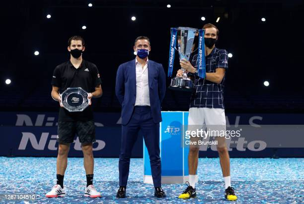 Daniil Medvedev of Russia poses with the winners trophy and Dominic Thiem of Austria poses with runners up plate with Andrea Gaudenzi, Chairman of...