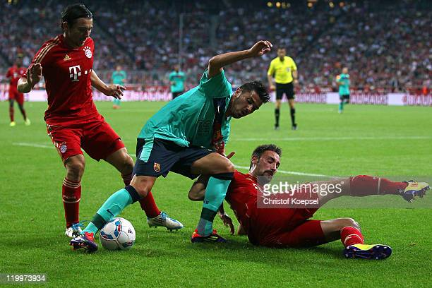 Danijel Pranjic of Bayern and Diego Contento of Bayern challenge David Villa of Barcelona during the Audi Cup final match between FC Bayern Muenchen...
