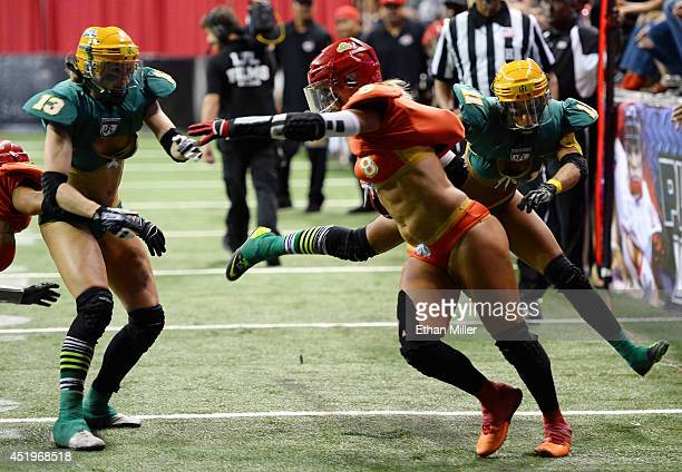 Danika Brace of the Las Vegas Sin gets away from Anna Heasman and Laure GelisDiaz of the Green Bay Chill to score a touchdown during their game at...