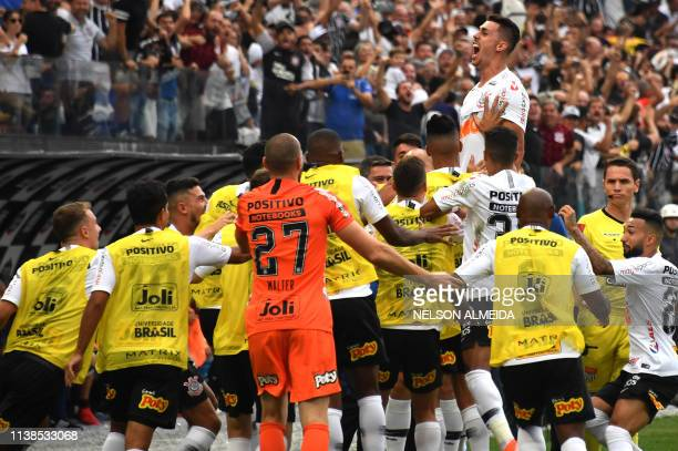 Danilo Avelar of Corinthians celebrates with teammates after scoring against Sao Paulo during the Paulista championship final football match held at...