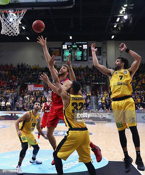 Danilo Barthel of Muenchen is challenged by Johannes Thiemann and Drew Crawford of Ludwigsburg during the easyCredit BBL match between MHP Riesen...