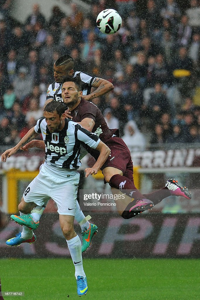 Danilo D Ambrosio (C) of Torino FC clashes with Claudio Marchisio (D) and Arturo Vidal (Up) of Juventus during the Serie A match between Torino FC and Juventus at Stadio Olimpico di Torino on April 28, 2013 in Turin, Italy.