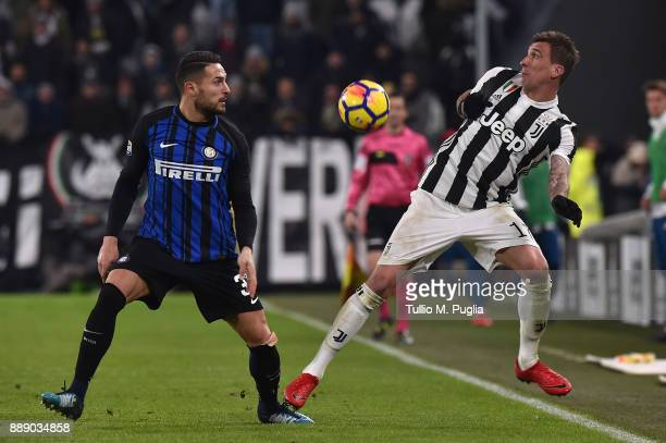 Danilo D'Ambrosio of Internazionale and Mario Mandzukic of Juventus compete for the ball during the Serie A match between Juventus and FC...