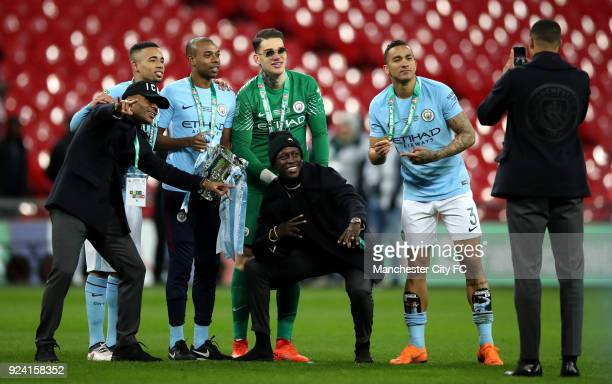 Danilo Ederson Fernandinho Gabriel Jesus Benjamin Mendy and Raheem Sterling of Manchester City pose for a photo with the trophy after winning the...