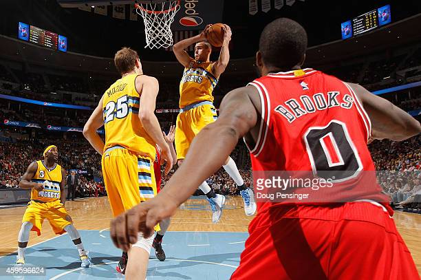 Danilo Gallinari of the Denver Nuggets grabs a rebound as Aaron Brooks of the Chicago Bulls, Timofey Mozgov and Ty Lawson of the Denver Nuggets...