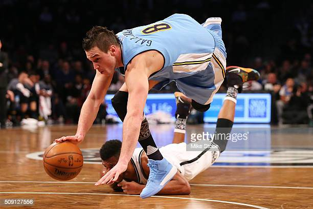 Danilo Gallinari of the Denver Nuggets is tripped up by Thaddeus Young of the Brooklyn Nets at the Barclays Center on February 8, 2016 in Brooklyn...