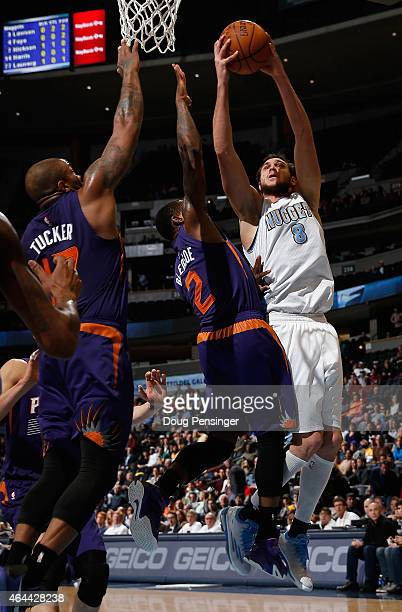 Danilo Gallinari of the Denver Nuggets puts up a shot against Eric Bledsoe of the Phoenix Suns at Pepsi Center on February 25 2015 in Denver Colorado...