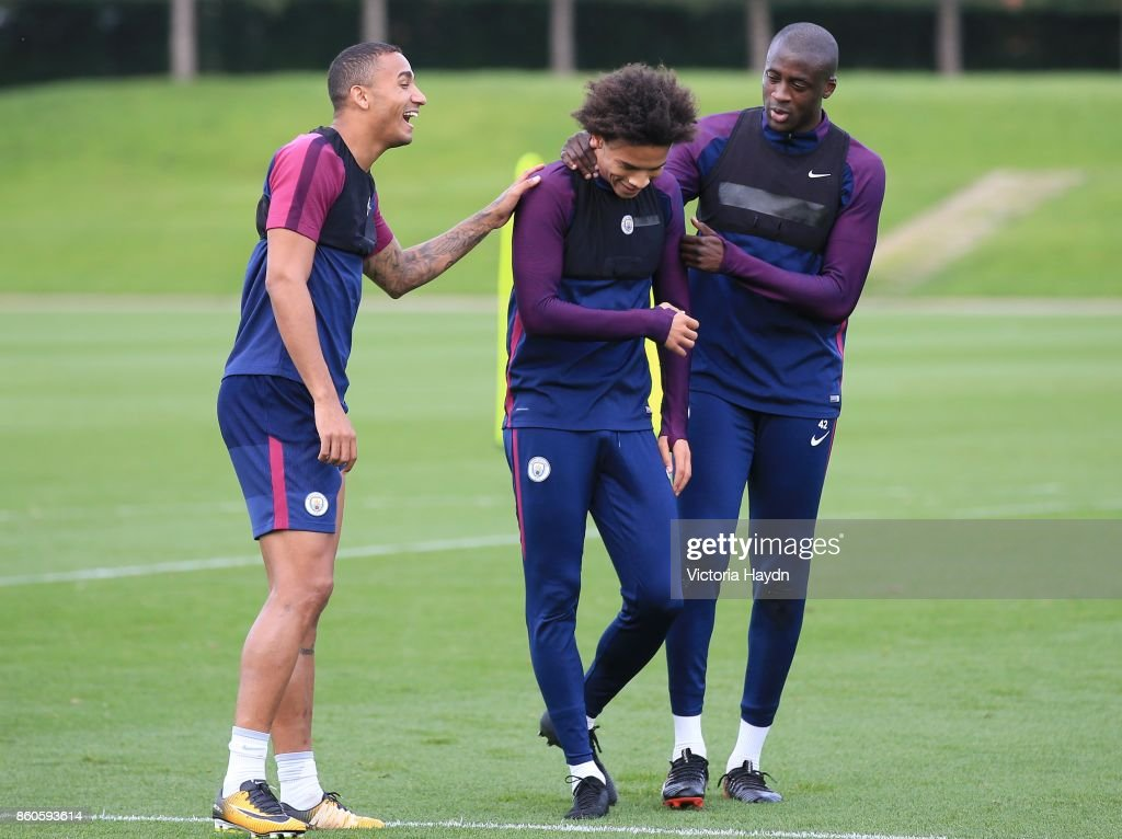 Danilo, Leory Sane and Yaya Toure joke during training at Manchester City Football Academy on October 12, 2017 in Manchester, England.