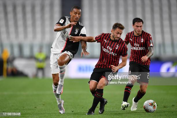 Danilo of Juventus is challenged by Hakan Calhanoglu of AC Milan during the Coppa Italia SemiFinal Second Leg match between Juventus and AC Milan at...