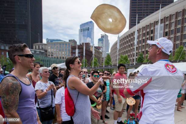 Danilo Pasano a professional pizza acrobat throws a pizza at Jessica Black an audience member during the first Boston Pizza Festival at City Hall...