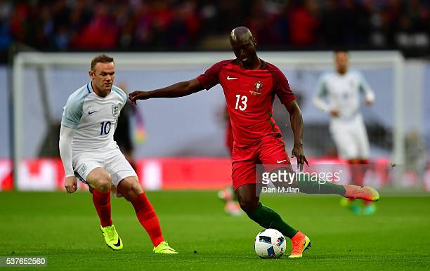 Danilo Pereira of Portugal is watched by Wayne Rooney of England during the international friendly match between England and Portugal at Wembley...