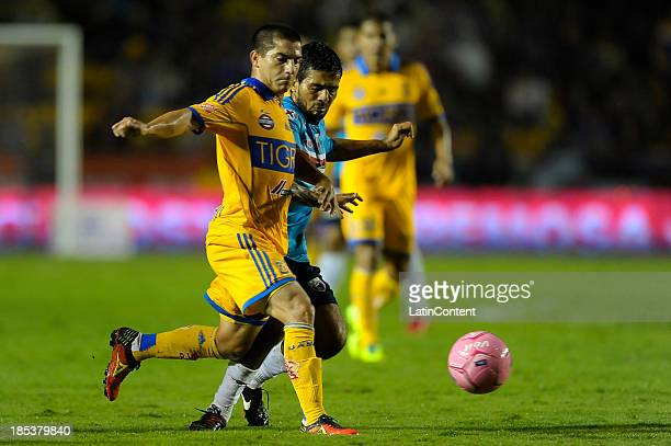 Danilo Verón of Tigres fights for the ball with Walter Erviti of Atlante during a match between Tigres UANL and Atlante as part of the Apertura 2013...
