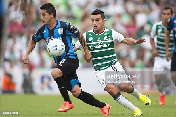 Danilo Veron of Queretaro vies for the ball with Juan Pablo Rodriguez of Santos during their Mexican Apertura tournament football match at the Corona...