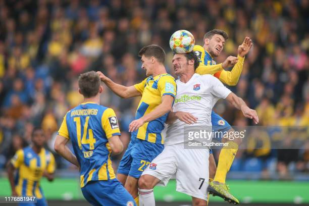 Danilo Wiebe and Benjamin Kessel of Eintracht Braunschweig fight for the ball with Dominik StrohEngel of SpVgg Unterhaching during the 3 Liga match...
