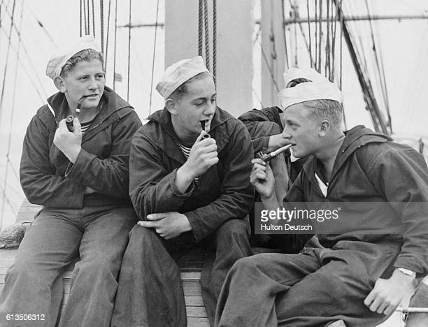 """Danish cadets on board the training ship """"Denmark"""" smoking their pipes in Falmouth, England."""