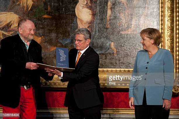 Danish cartoonist Kurt Westergaard receives the award from German Chancellor Angela Merkel and Joachim Gauck during the M110 Media Award ceremony at...