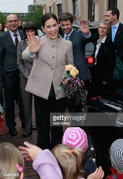 Danish Crown Prince Frederik and Danish Crown Princess Mary who is pregnant with twins greet onlookers upon their arrival at the High School for...