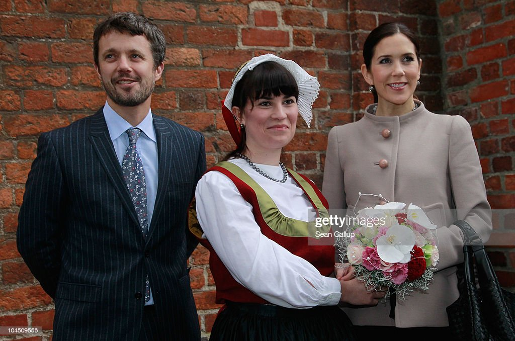 Danish Crown Prince Frederik and Danish Crown Princess Mary (R), who is pregnant with twins, receive flowers from a woman wearing local, traditional folk dress upon the royal couple's arrival on September 28, 2010 in Guestrow, Germany. Prince Frederik and Princess Mary are on a two-day visit to northern Germany.