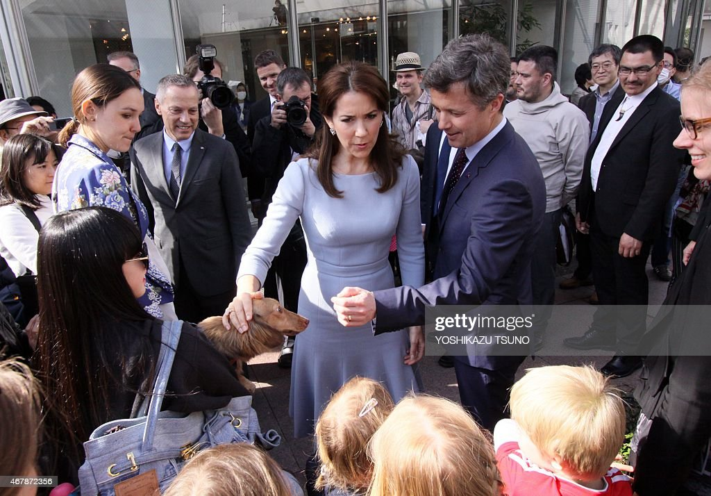 Danish Crown Prince Frederik (centre R) and his wife Crown Princess Mary (centre L) chat with Japanese and Danish children after they inspected a cardboard igloo near the Danish embassy in Tokyo on March 28, 2015. The Danish royal couple are on a three-day visit to promote Greenland. AFP PHOTO / Yoshikazu TSUNO