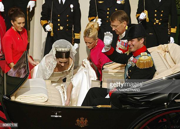 Danish Crown Prince Frederik waves while his wife Princess Mary Elizabeth Donaldson of Australia collects her long dress to step up in to the horse...