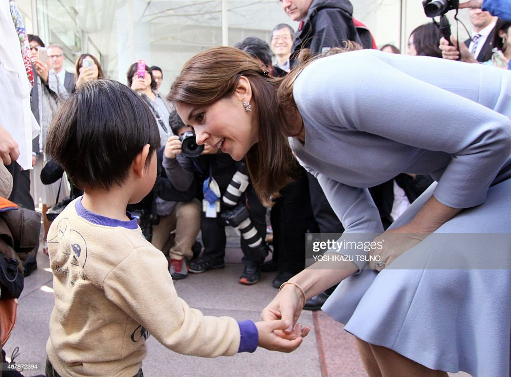 Danish Crown Princess Mary (R) chats with a Japanese child after she and her husband Crown Prince Frederik inspected a cardboard igloo near the Danish embassy in Tokyo on March 28, 2015. The Danish royal couple are on a three-day visit to promote Greenland. AFP PHOTO / Yoshikazu TSUNO