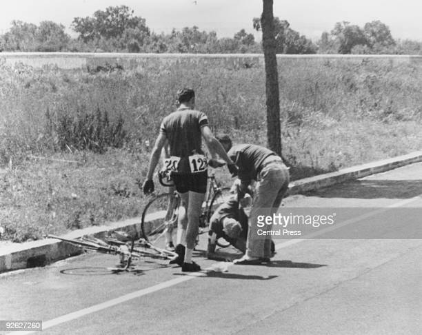 Danish cyclist Knud Enemark Jensen is attended by a Danish official after collapsing with heat stroke and suffering a fractured skull during the 100...