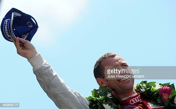 Danish driver Tom Kristensen celebrates on the podium after coming in second in the 82nd 24 Hours of Le Mans endurance race on June 15 in Le Mans...