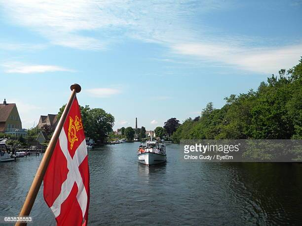 Danish Flag On Ferry Boat In River Against Sky
