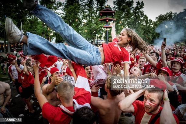 Danish football fans react to their team's first goal as they watch the UEFA EURO 2020 semi-final football match between England and Denmark on the...