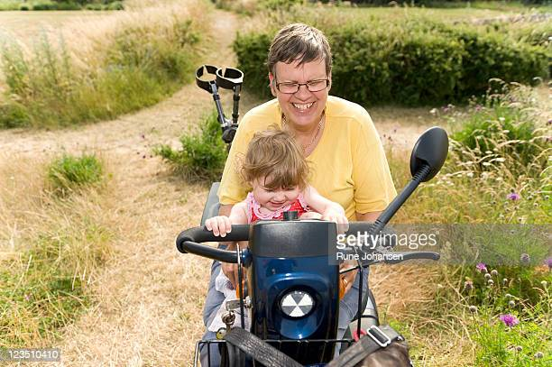 danish girl, 1 years old, sitting with her grandmother, 59 years old, who has multiple sclerosis in her motorized cart - 55 59 years stock pictures, royalty-free photos & images