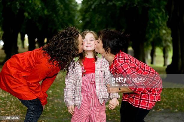 Danish girl, 5 years, old being kissed on the cheek by her mother, 27 years old, and grandmother, 53 years old, at Frederiksberg Park, Copenhagen, Denmark