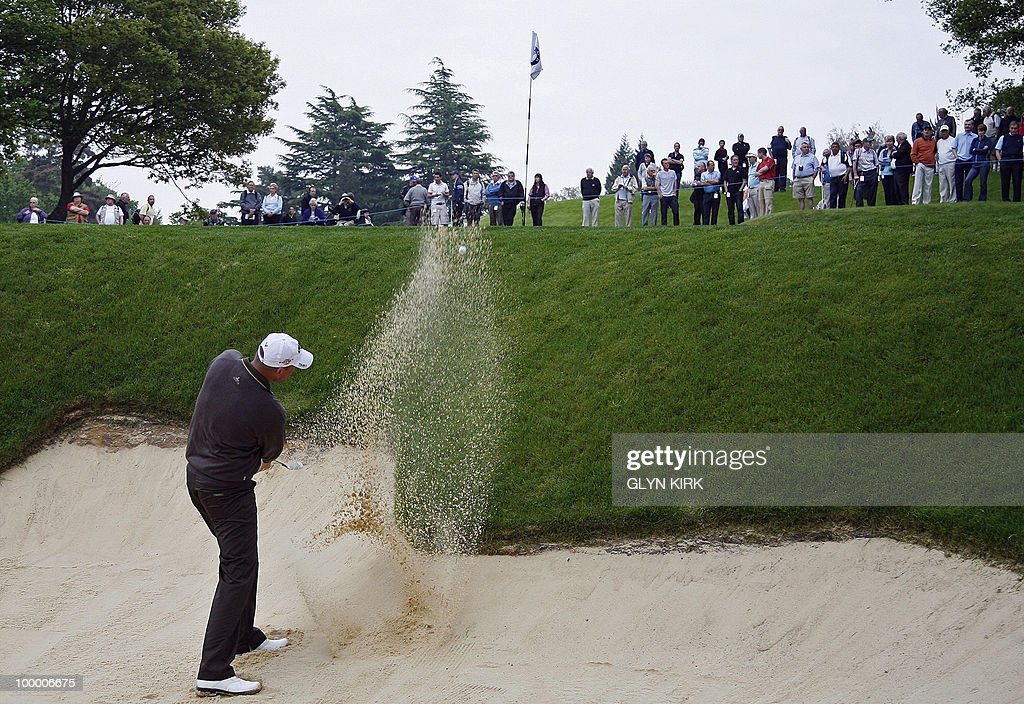 Danish golfer Thomas Bjorn plays out of a bunker at the 2nd green on the first day of the PGA Championship on the West Course at Wentworth, central England, on May 20, 2010.