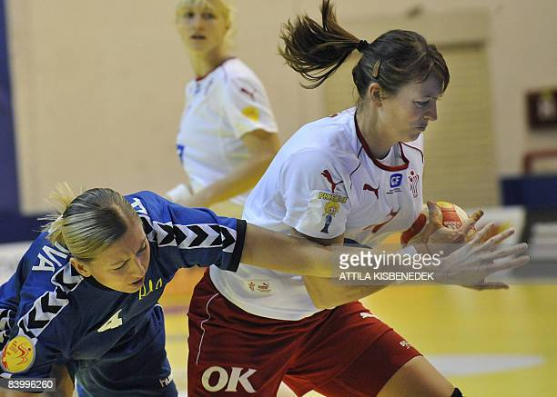 Danish Lene Nielsen fights for the ball with Ukrainian Anastasiia Pidpalova during the 8th Women's Handball European Championships match on December...