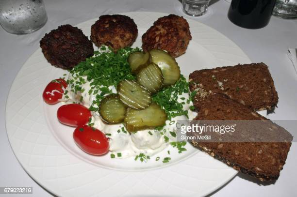 Danish meatballs (frikadeller) served with pickled cucumber salad, potato salad, plum tomatoes and rye bread