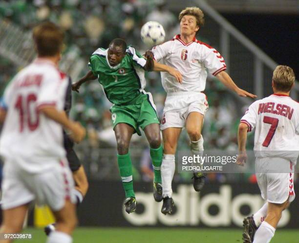 Danish midfielder Thomas Helveg heads off the ball with Nigerian forward Rasheed Yekini 28 June at the Stade de France in SaintDenis during their...