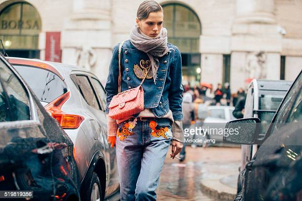 Danish model Caroline Brasch Nielsen exits the Ferragamo show at Piazza Affari wearing an embroidered denim jacket and jeans and a pink Chanel purse...