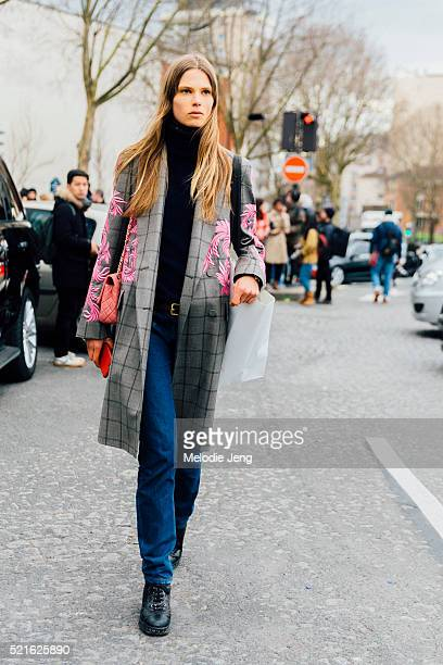 Danish model Caroline Brasch Nielsen wears a gray Dries Van Noten plaid coat with pink floral embroidery and jeans after the Celine show at Tennis...