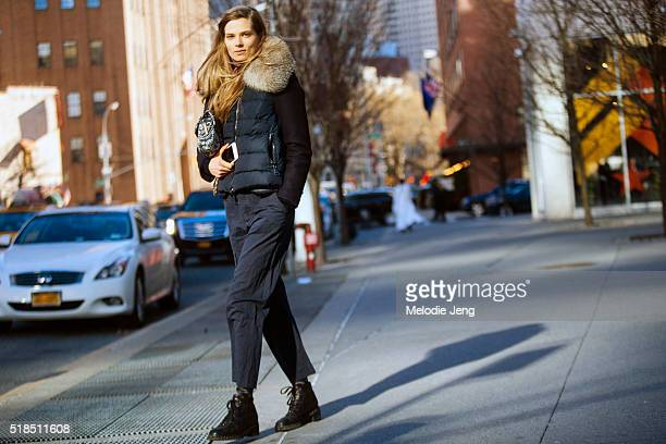 Danish model Caroline Brasch Nielsen wears a Moncler blue puffer vest with a fur collar a blue Chanel purse loose fit blue trousers and black boots...