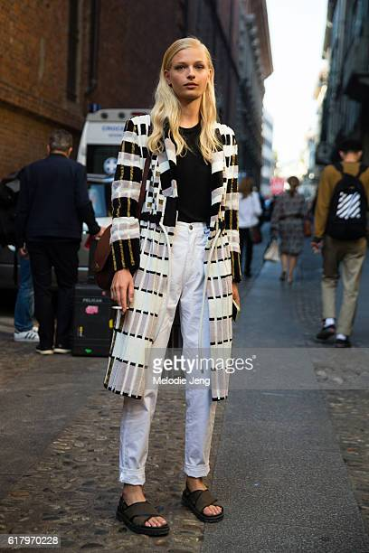 Danish model Frederikke Sofie wears a black and white Freya Dalsjø jacket black top white jeans a brown Celine purse and green sandals after the...